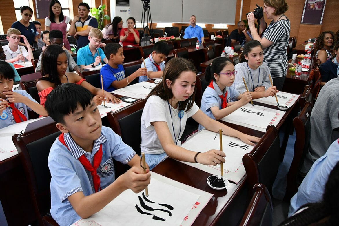 American and Chinese schoolchildren work side-by-side during a demonstration of Chinese calligraphy at a Dongcheng Educational Group magnet school in Hangzhou, China, in July. (MTSU photo by Andrew Oppmann)