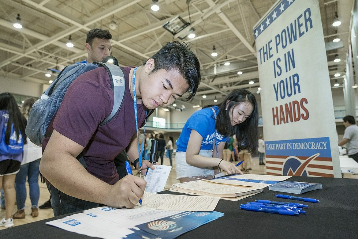 Incoming MTSU students Skyler Senesombath and Amy Lin register to vote as Zachary Brow awaits his turn at one of the True Blue Voter registration tables available this summer at the Campus Recreation Center during the CUSTOMS new student orientation sessions. Almost 200 students were registered during the ongoing initiative in partnership with the Rutherford County Election Commission. (MTSU file photo by J. Intintoli)