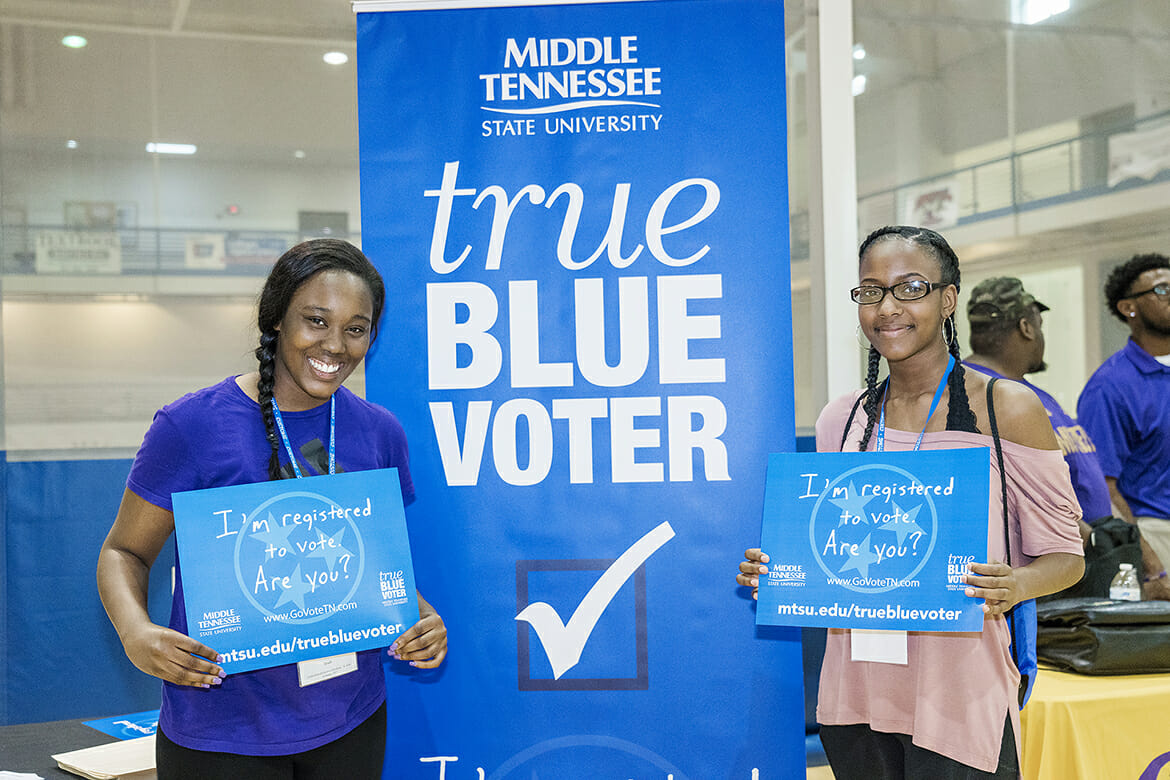 "Incoming MTSU freshmen Amarya Zachery, left, and her sister, Tierany Zachery, hold up ""I'm registered to vote"" signs after registering at one of the True Blue Voter registration tables available this summer at the Campus Recreation Center during the CUSTOMS new student orientation sessions. Almost 200 students have been registered during the ongoing initiative in partnership with the Rutherford County Election Commission. (MTSU photo by J. Intintoli)"