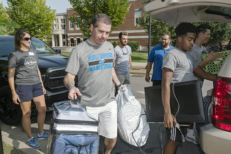 Nick McDevitt, center, MTSU head men's basketball coach, helps unload a vehicle filled with a student's belongings Friday, Aug. 24, outside Corlew Hall during the annual We-Haul move-in event. Volunteers helped hundreds of students get settled into their dorms in preparation for the start of fall semester classes Monday, Aug. 27. (MTSU photo by J. Intintoli)