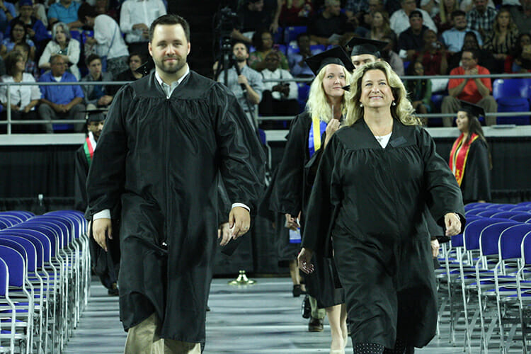 Dr. Tyler Henson, left, director of the MT One Stop, and Yvonne Elliott, right, executive aide for the Center for Popular Music at MTSU, guide members of a graduating class into Murphy Center as heralds for a recent university commencement ceremony. The pair will help graduating students celebrate again Saturday, Dec. 15, at the university's dual fall 2018 commencement ceremonies. (MTSU file photo by GradImages)