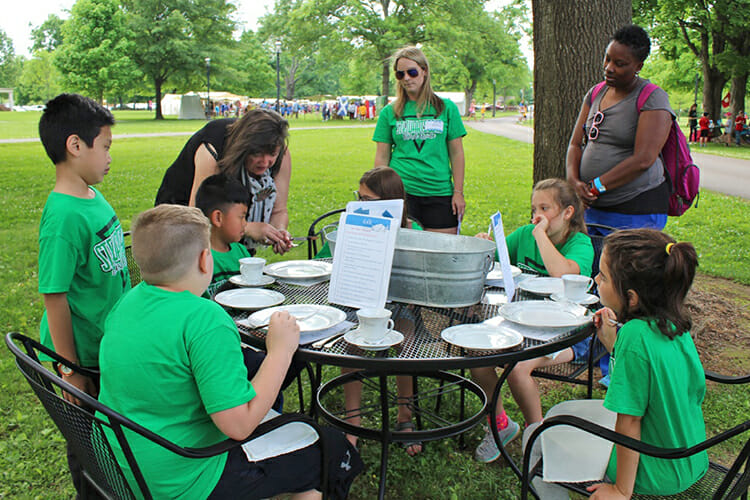 "Professor Deborah Belcher, center left, chair of the MTSU Department of Human Sciences, shows youngsters the art of properly setting a table during the 2017 ""Day of Washing, Churning and Learning"" at Oaklands Mansion in Murfreesboro. (Photo submitted)"