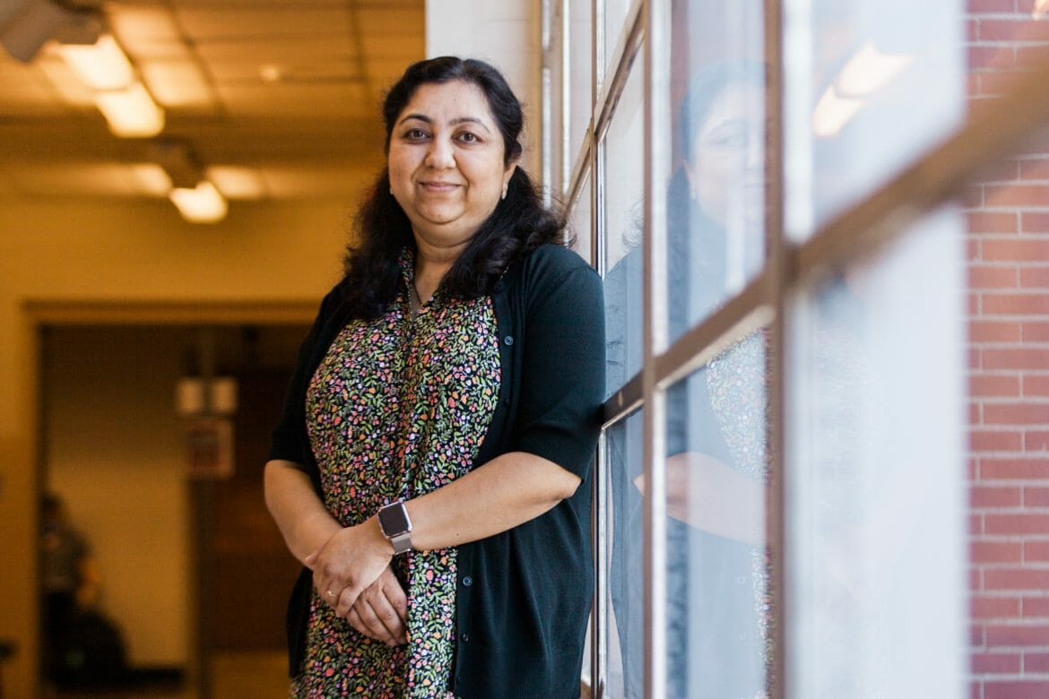 Photo of Dr. Medha Sarkar, professor of Computer Science at MTSU, standing in front of a large window in a hallway in the Kirksey Old Main building on the MTSU campus.
