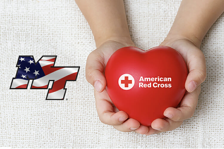 blood drive promo showing hands holding Red Cross heart alongside the MT logo with the American flag inside