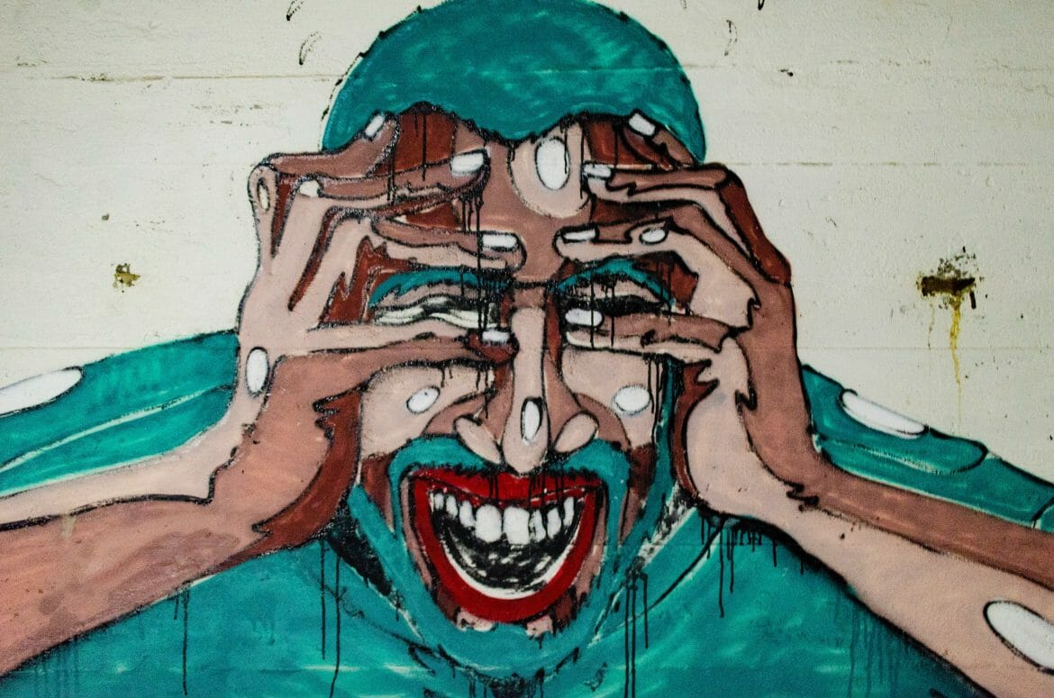 Graffiti art of man yelling and grabbing his head with his hands. Photo by Aaron Blanco Tejedor on Unsplash.