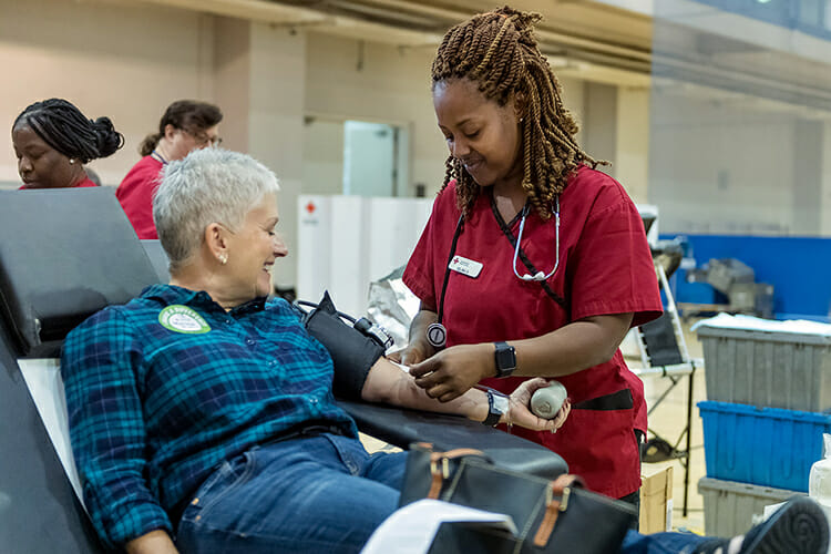 "MTSU supporter Martha Tolbert, left, watches Oct. 30 while American Red Cross phlebotomist Selina Davis helps her finish donating a pint of blood at the annual ""Bleed Blue, Beat WKU"" drive in the university's Campus Recreation Center. MTSU won the competition with Western Kentucky for the sixth time with 603 pints of whole blood donated Oct. 29-31. (MTSU photo by J. Intintoli)"