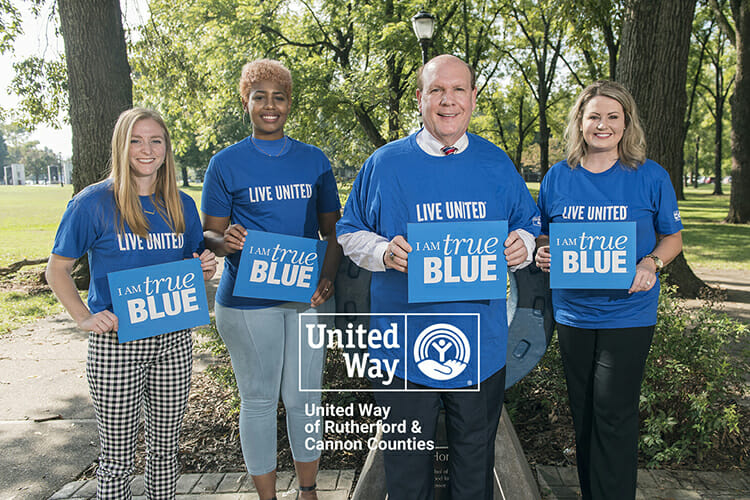 MTSU and United Way of Rutherford and Cannon Counties have partnered to encourage the campus community to use the nonprofit's Volunteer Connect website to find and register for volunteer opportunities. Pictured, from left, holding True Blue signs and wearing