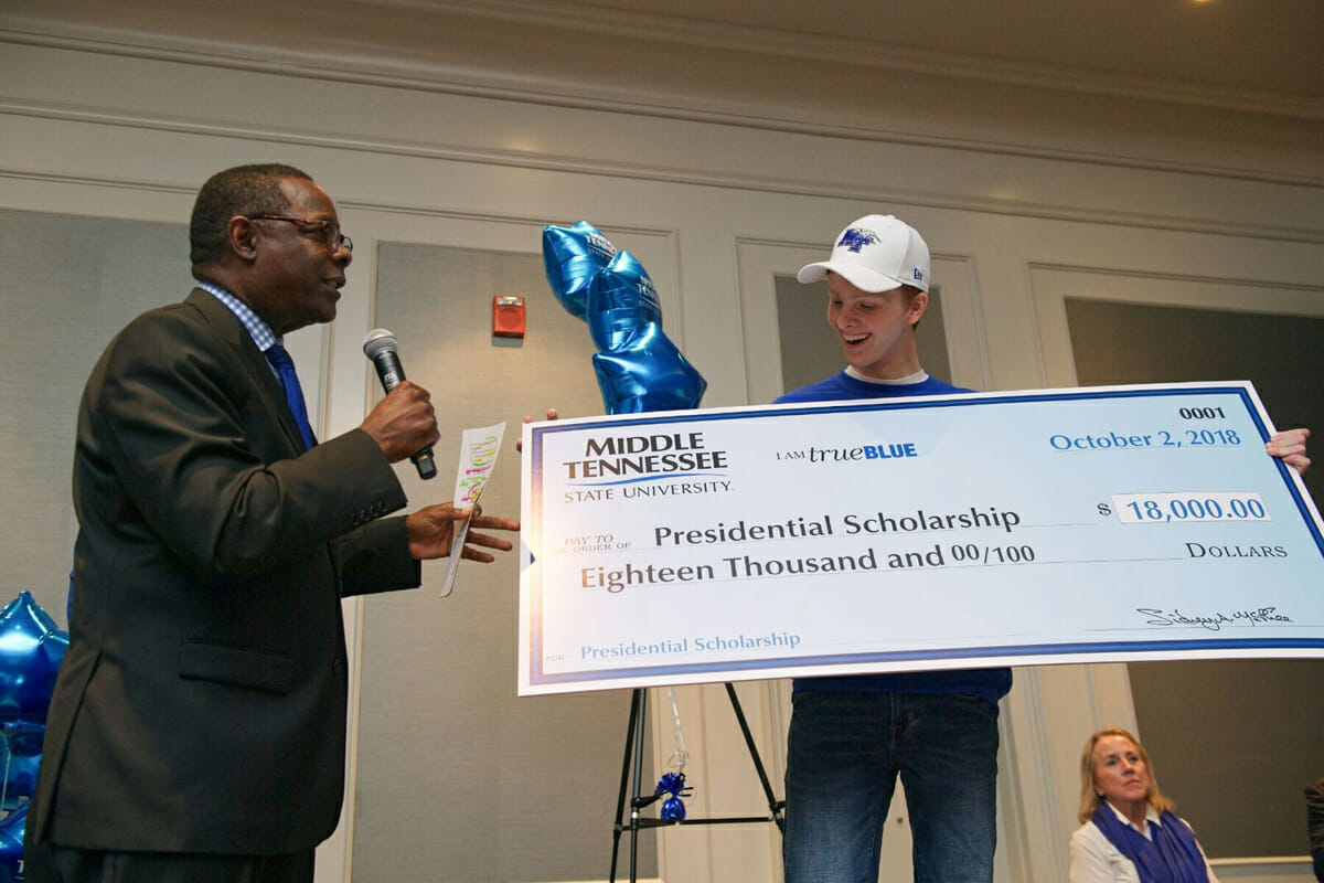 Grant Hampton, 18, right of Thompson's Station, Tenn., an Independence High School graduate who is now an MTSU freshman, smiles while holding a large replica of an $18,000 check representing the new expanded Presidential Scholarship announced by MTSU President Sidney A. McPhee in early October 2018 during the MTSU True Blue Tour visit to Franklin, Tenn. On the first 2019 tour stop in Murfreesboro, McPhee will announce the creation of yet another new guaranteed scholarship that will make a whole new group of high achievers scholarship-eligible for the first time. (MTSU file photo by Andy Heidt)