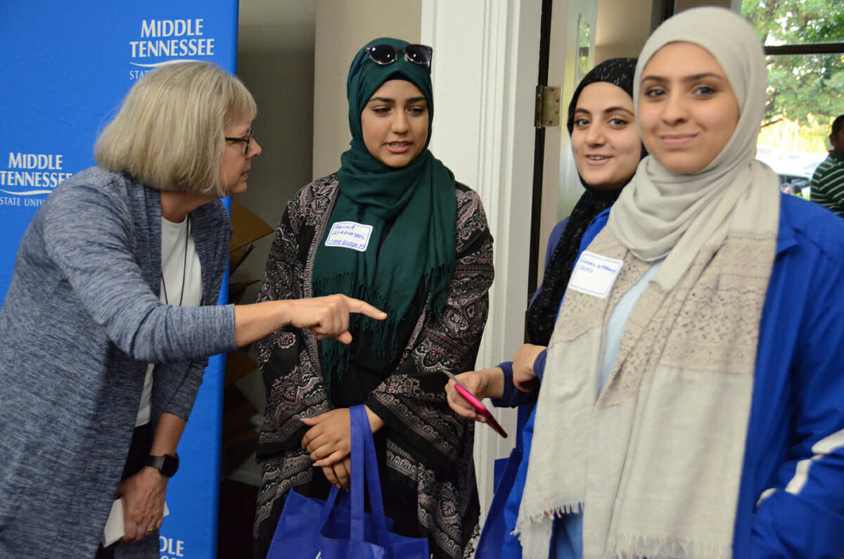 Deb Sells, left, vice president of Student Affairs at MTSU, advises prospective students from Nashville on which direction to head as they enter the True Blue Tour ballroom in October 2018 at the Millennium Maxwell House Hotel in Nashville. The students included Amina Al-Kharsani and Zanah Al-Rabiey of Cane Ridge High School and Fatima Al-Fatlawy of Overton High School. Al-Kharsani and Al-Fatlawy are MTSU freshmen this fall. MTSU and the tour return to Nashville Tuesday, Oct. 22. (MTSU file photo by Randy Weiler)