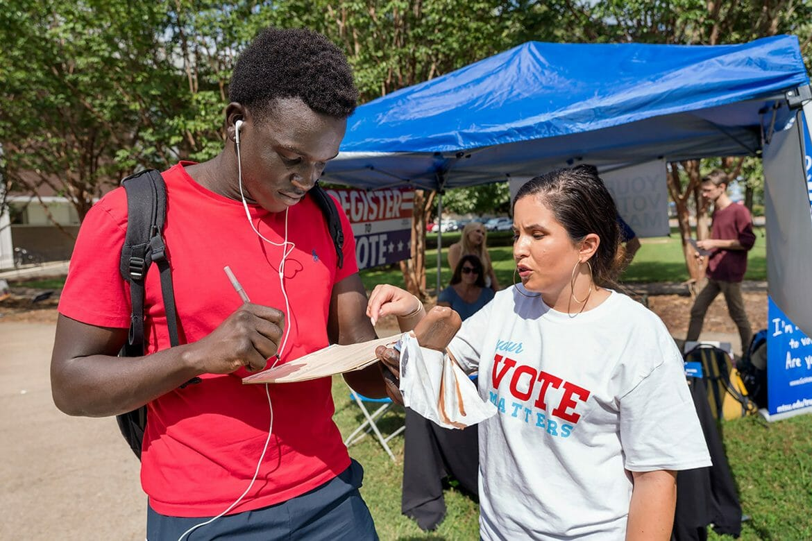 """Athaiy Othow, left, a freshman mechanical engineering technology major from Gallatin, Tenn., gets help Oct. 8 outside Peck Hall from Monica Haun, a political science major from Knoxville and president of the MTSU American Democracy Project and the university's Campus Election Engagement Project fellow, as he double-checks his new voter registration form to submit by Tennessee's Oct. 9 deadline for the 2018 midterm elections. MTSU has been encouraging students, faculty, staff and visitors to register to vote or update their voter registration information since June as part of the university's """"True Blue Voter Initiative."""" (MTSU photo by J. Intintoli)"""