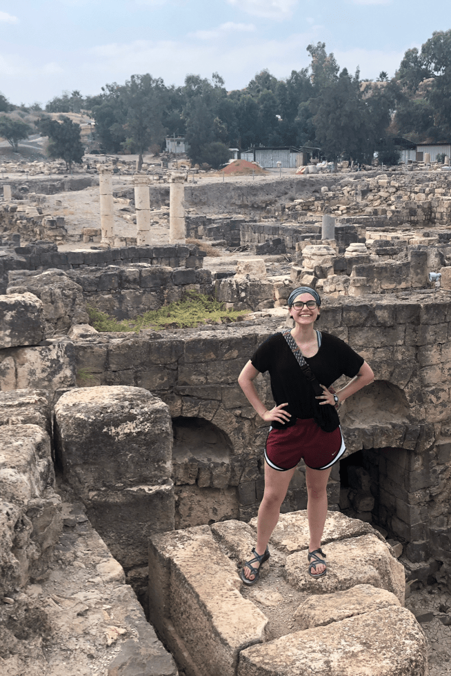 Hannah Solima stands in front of ancient ruins while abroad.