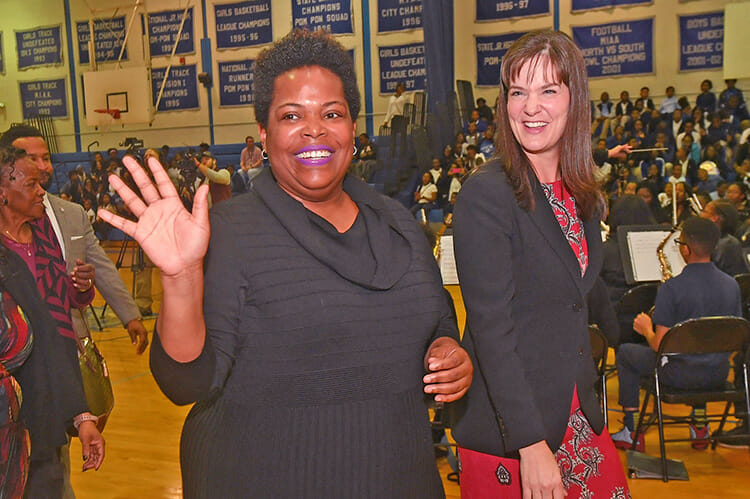 MTSU alumna Erica Stephens (Class of '02) waves to the crowd after the surprise Oct. 25 announcement at an all-school assembly that she was a winner of the prestigious Milken Educator Award, a national honor that comes with a $25,000 financial prize. Stephens is a fourth-grade math teacher at John P. Freeman Optional School in Memphis, Tenn. At right is Tennessee Education Commissioner Candice McQueen. (Photo courtesy of the Milken Family Foundation)