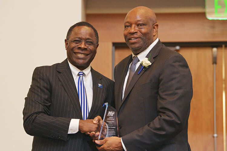 In this February 2018 file photo, MTSU President Sidney A. McPhee, left, presents MTSU assistant track and field coach Raymond Bonner with the Unsung Hero Award for his excellence in sports at the annual Unity Luncheon inside the Student Union Ballroom. (MTSU file photo by Andy Heidt)