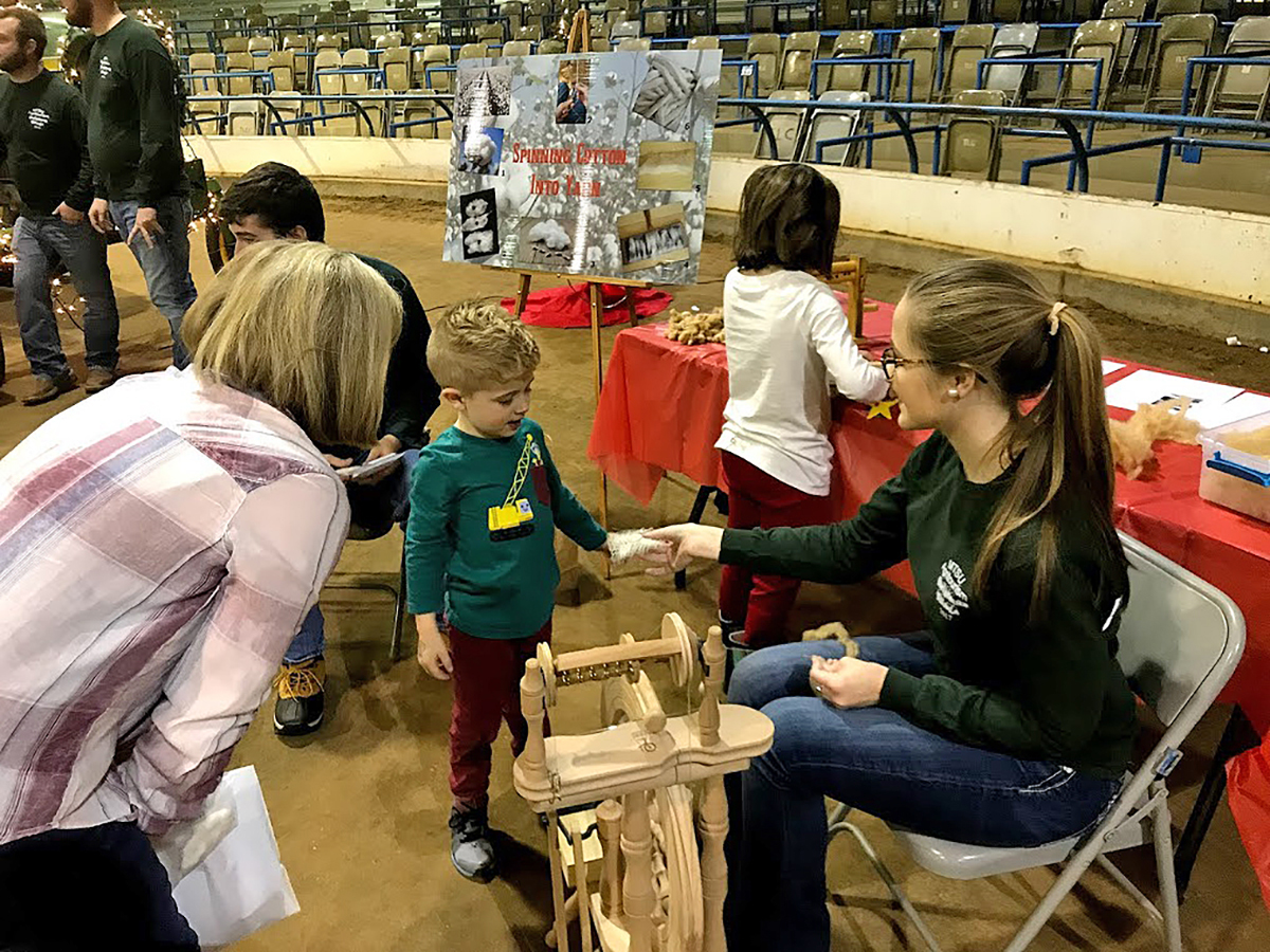 MTSU School of Agriculture student Rachel Elrod, right, shows a small child a small piece of cotton she had spun on the spinning wheel and gave it to the youngster during the Christmas Village.