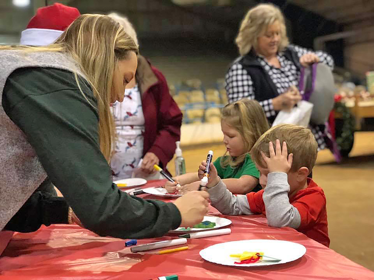 An MTSU agritourism class member assists a little boy in making a Christmas craft during the annual Winter Village, formerly called Christmas Village, held in December 2018 in the Tennessee Livestock Center. This year's event will be held from 9 a.m. to noon on Saturday, Dec. 7. (Submitted photo)