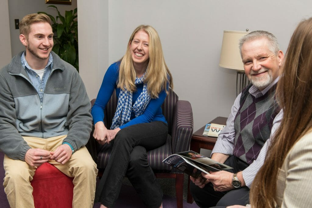Master of Business Education professor, Vince Smith, sitting and talking with his graduate assistants (l to r): Nick Wise, Amanda Goodman, Professor Vince Smith, Stephanie Keys. Photo by Kimi Conro.