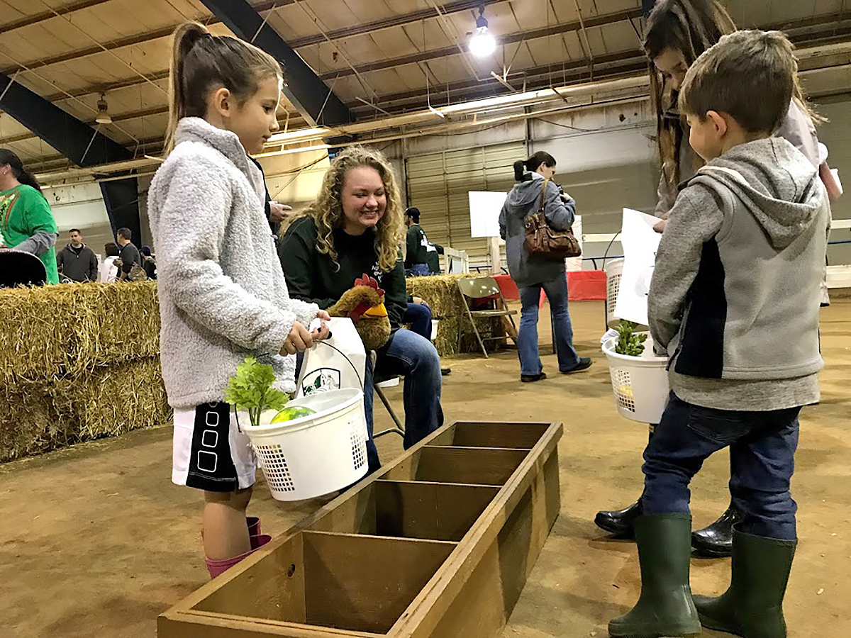 MTSU then-freshman animal science major Jessika Benson, seated and second from left, assists children visiting the Little Acres area during the December 2018 Christmas Village in the Tennessee Livestock Center. Children could collect fruit and vegetables, milk a cow and more in the area. Now called Winter Village, the 2019 event will be held Saturday, Dec. 7. (Submitted photo)