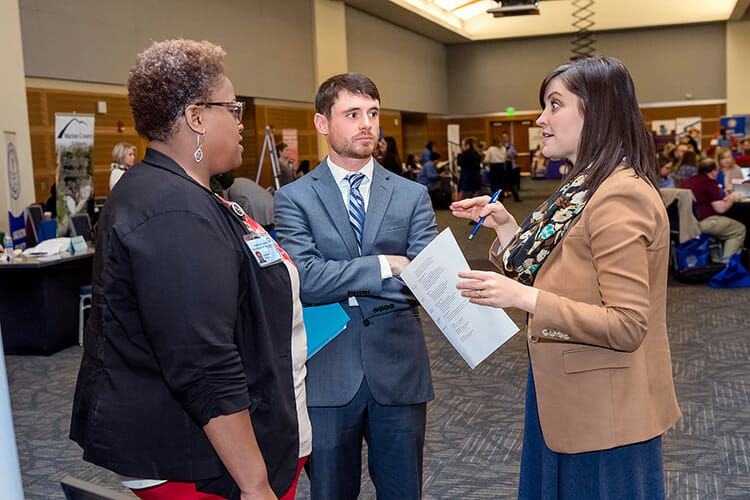 Luronda Jennings, left, and Erin Harrell, right, from Hamilton County Schools talk with student teacher Preston O'Neal about employment opportunities at the MTSU College of Education's Student Teacher Seminar and Recruitment Fair held Wednesday, Dec. 12, in the Student Union Ballroom. Employers from across the region and as far as China came to meet with graduating student teachers. (MTSU photo by J. Intintoli)
