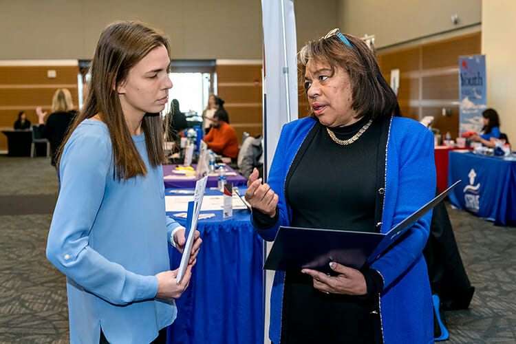 MTSU senior Kellie Kosar, left, talks with Patricia Cunningham from Washington D.C. Public Schools System about employment opportunities at the MTSU College of Education's Student Teacher Seminar and Recruitment Fair held Wednesday, Dec. 12, in the Student Union Ballroom. Employers from across the region and as far as China came to meet with graduating student teachers. (MTSU photo by J. Intintoli)