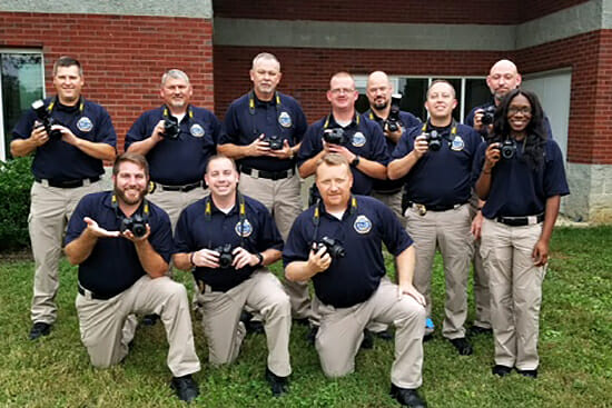 Some members of the Nov. 1, 2018, graduating class at the Tennessee Bureau of Investigation State Academy pose with the more sophisticated cameras provided to them by MTSU's Department of Criminal Justice Administration to complete their course work. (Photo submitted)