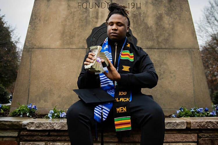 """MTSU senior BryTavious """"Tay Keith"""" Chambers of Memphis, a platinum-selling and now Grammy-nominated rap producer who'll graduate Saturday, Dec. 15, with a degree in integrated studies from the University College, poses at the MTSU obelisk on East Main Street in his graduation regalia. (Photo copyright Devin P. Grimes)"""