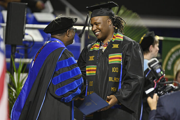 "MTSU senior BryTavious Chambers of Memphis, known professionally as ""Tay Keith,"" accepts his bachelor's degree in integrated studies from President Sidney A. McPhee during the university's fall 2018 commencement ceremonies Saturday, Dec. 15. Chambers earned his degree from MTSU's University College the same month a rap single he produced, Travis Scott's ""SICKO MODE,"" went double platinum and No. 1 on the Billboard Hot 100 chart and was nominated for two Grammy Awards. (MTSU photo by Andy Heidt)"