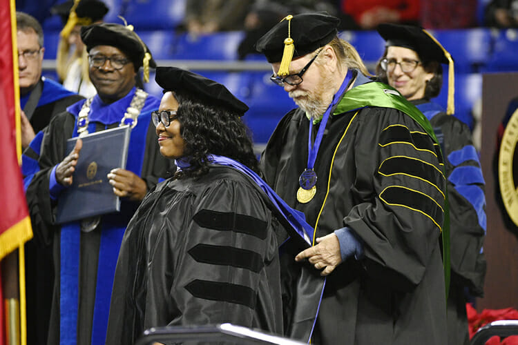 Marquita R. Reed, center, smiles with pride as Carroll Van West, head of MTSU's Center for Historic Preservation and a lead professor in the Public History Program, helps her don her doctoral hood Saturday, Dec. 15, at the university's fall 2018 morning commencement ceremony in Murphy Center. Looking on are, from left, University Provost Mark Byrnes, MTSU President Sidney A. McPhee and Cheryl B. Torsney, vice provost for faculty affairs. Reed, who is collections manager at the National Museum of African American Music in Nashville, was one of 260 graduate students and 1,471 undergraduates receiving their degrees in Saturday's dual ceremonies. (MTSU photo by Andy Heidt)
