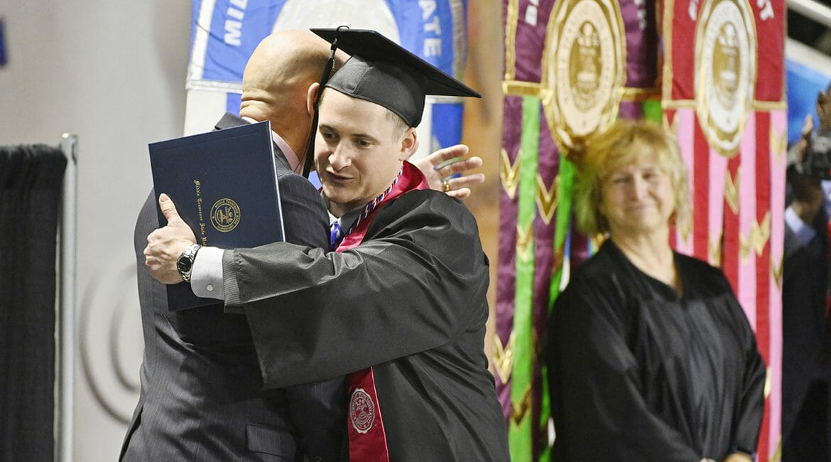 U.S. Army veteran Jay Strobino, new bachelor's degree in exercise science in hand, gets a hug from retired U.S. Army Lt. Gen. Keith Huber, left, as Huber's assistant, Pat Thomas, looks on during MTSU's fall 2018 afternoon commencement ceremony in Murphy Center. Huber, MTSU's senior adviser for veterans and leadership initiatives, has been advising Strobino on post-graduation career options with the help of the Charlie and Hazel Daniels Veterans and Military Family Center on campus. (MTSU file photo by Andy Heidt)