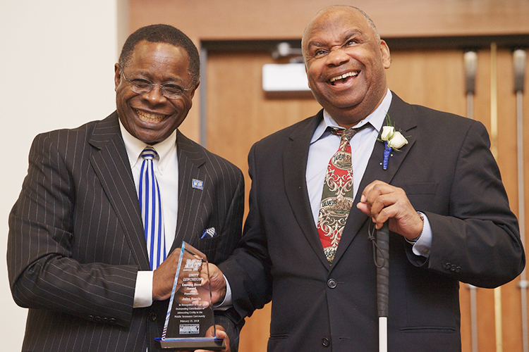 "MTSU President Sidney A. McPhee, left, and John Harris, founding director of the university's Disability and Access Center, laugh together Feb. 15, 2018, during the Unity Luncheon. Harris, an MTSU alumnus who retired in 2013 from his post after more than 27 years establishing and expanding services for students with disabilities, was one of six local residents honored at the 2018 event as ""unsung heroes"" serving the community. (MTSU file photo by Andy Heidt)"