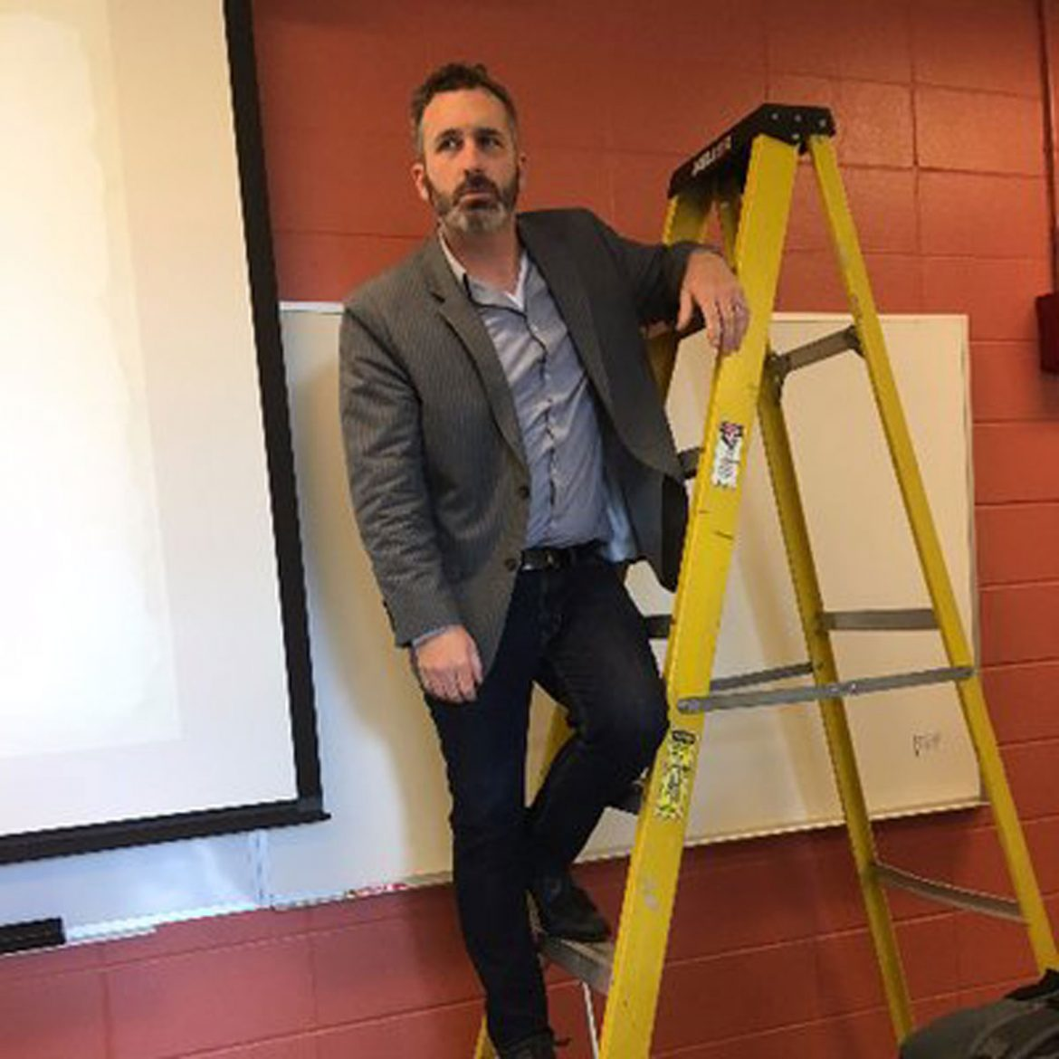 Portrait of Ben Sawyer, professor of History at MTSU, being funny by standing on a ladder in a classroom.