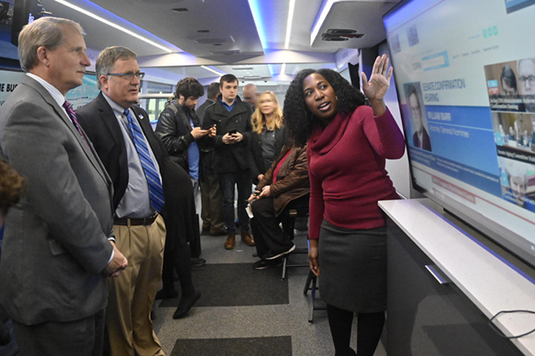 Jenae Green, right, a C-SPAN marketing specialist, explains the C-SPAN website to Rutherford County Mayor Bill Ketron, left, and MTSU Provost Mark Byrnes aboard the C-SPAN Bus Jan. 16. (MTSU photo by J. Intintoli)