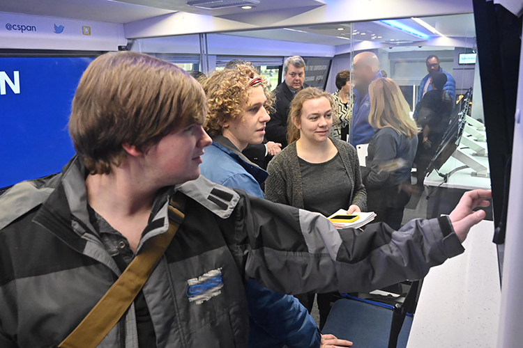Students Timothy Eichstaedt and John Cantor and Sidelines reporter Ashley Perham check out an interactive display on the C-SPAN Bus, which stopped at MTSU Jan. 16. (MTSU photo by J. Intintoli)