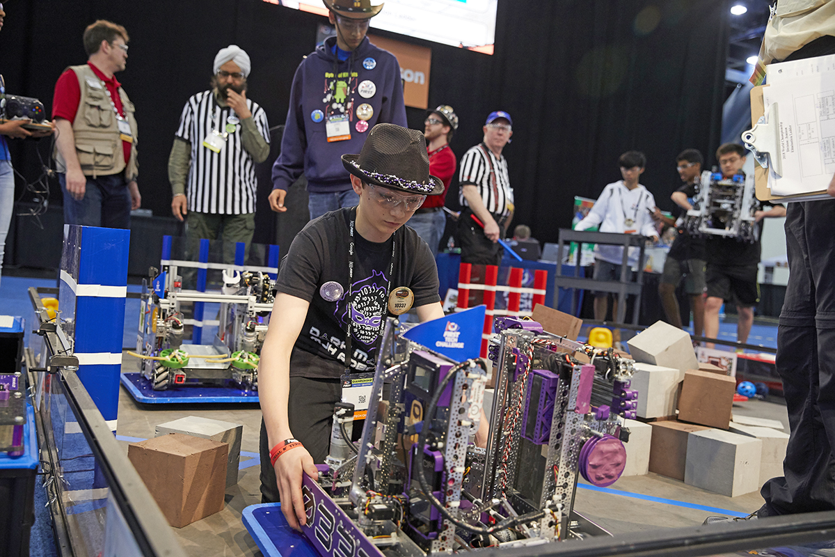 A participant lifts his team's robot.