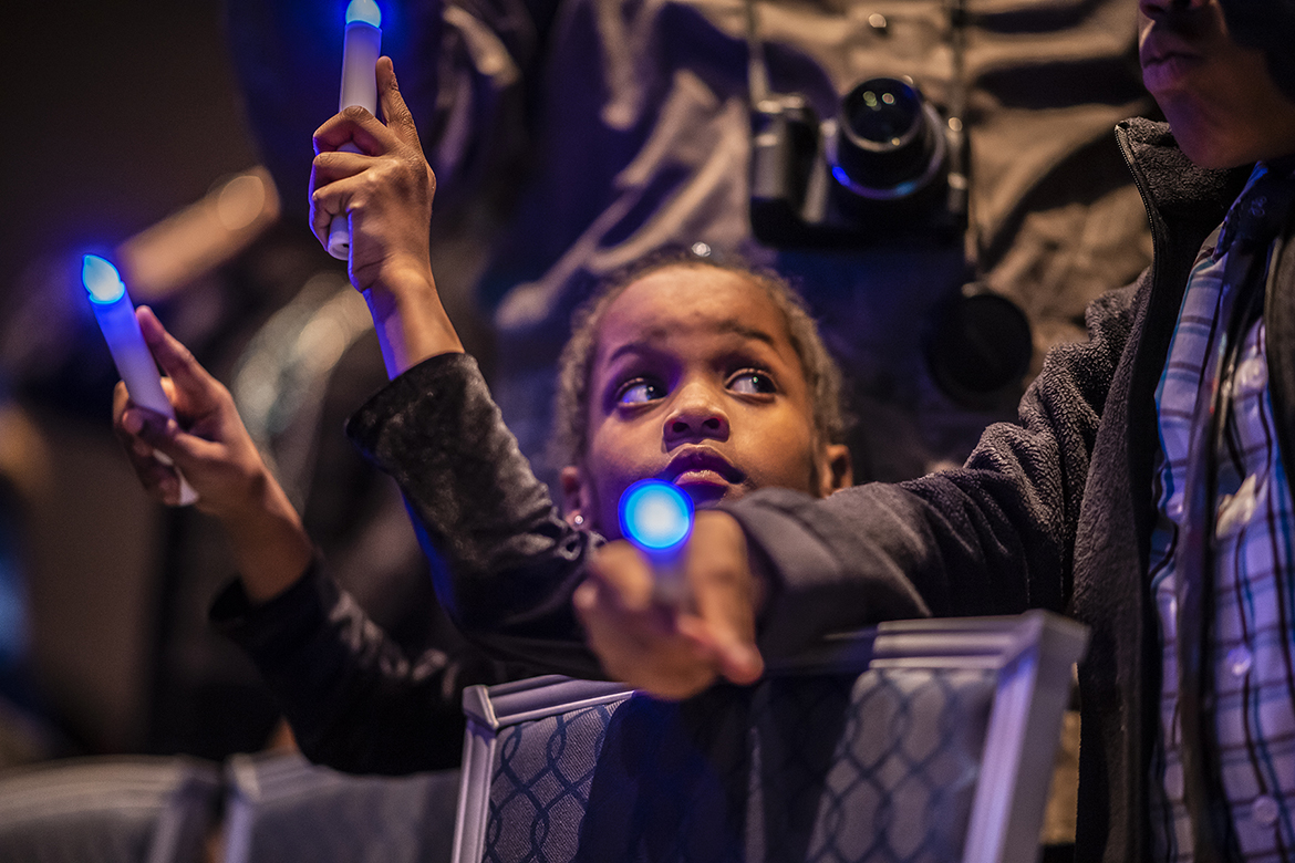A young attendee holds two electronic blue candles during MTSU's 2019 MLK Candlelight Vigil Monday night inside the Student Union Ballroom. (MTSU photo by Eric Sutton)
