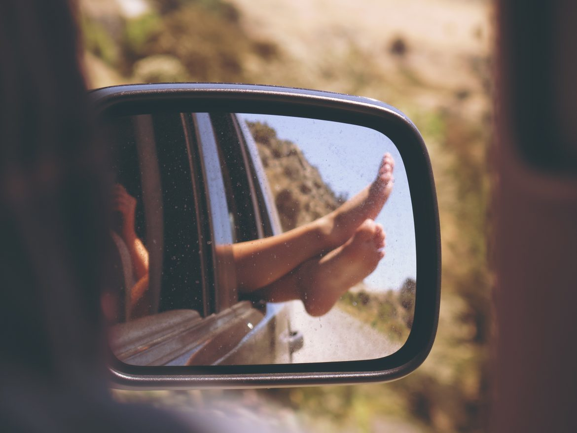 Image of a rear-view mirror on a car that shows a young person's feet hanging out of the window while driving. Photo by anja. on Unsplash