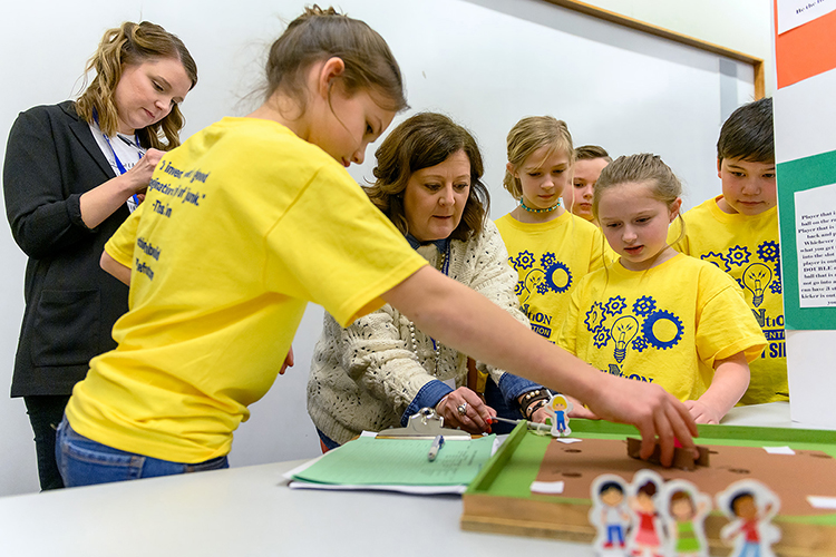 "MTSU Invention Convention judges Katie Schrodt, left, a Department of Elementary and Special Education professor, and Middle Tennessee Christian School Principal Melanie Maxwell, center, play with the ""Kickball King"" board game invented by Erma Siegel Elementary fourth-graders Aurora Nelson-Keener, Lillian Bunney and Claire Couey as some of their classmates watch Feb. 21 in the Student Union Ballroom. Aurora, Lillian and Claire's game won a ribbon as a ""Judges' Favorite"" in the Fourth Grade Games category. (MTSU photo by J. Intintoli)"