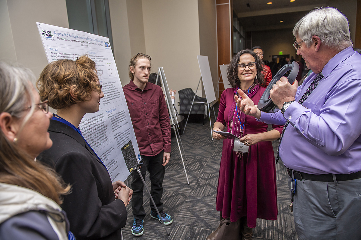 "MTSU's Neal McClain, right, a director of the computer science lab in the James E. Walker Library, helps explain the ""Augmented Reality to Improve Student STEM Success"" research project to Ilana Horn, professor of mathematics education at Vanderbilt University's Peabody College, in February 2019 on Day 1 of the Tennessee STEM Education Center's 13th annual research conference in the Student Union Building. Listening are McClain's faculty and student partners in the project: professor Amy Phelps, left, Myranda Uselton and Levi Madden. The 2020 conference will be Jan. 16-17 at Tennessee Tech in Cookeville, Tenn. (MTSU file photo by Eric Sutton)"
