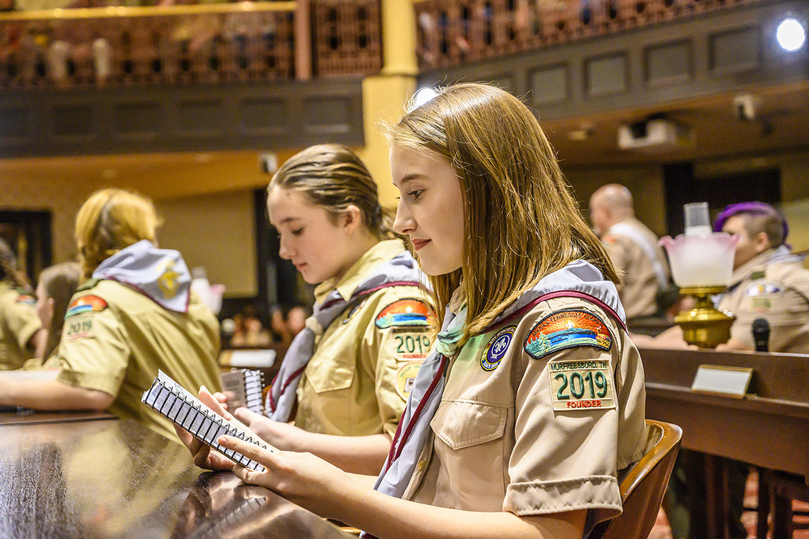 Newly inducted members of all-girl Troop 2019 of Scouts BSA examine the handbooks they were presented as part of their unit's charter ceremony. (MTSU photo by Eric Sutton)