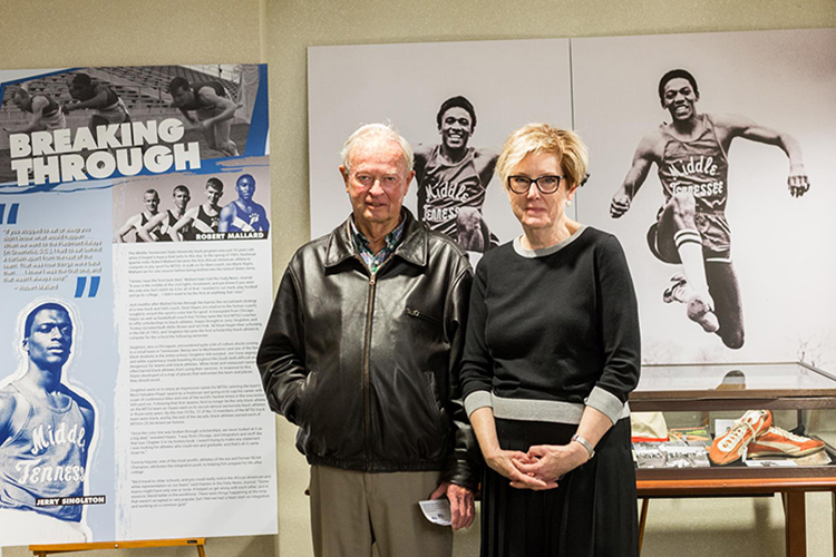 Legendary MTSU track and field coach Dean Hayes, left, stands with Bonnie Allen, dean of the James E. Walker Library, in front of a current library exhibit chronicling highlights and milestones in Hayes' career and in the history of the university's track and field program. (Photo courtesy of GoBlueRaiders.com)