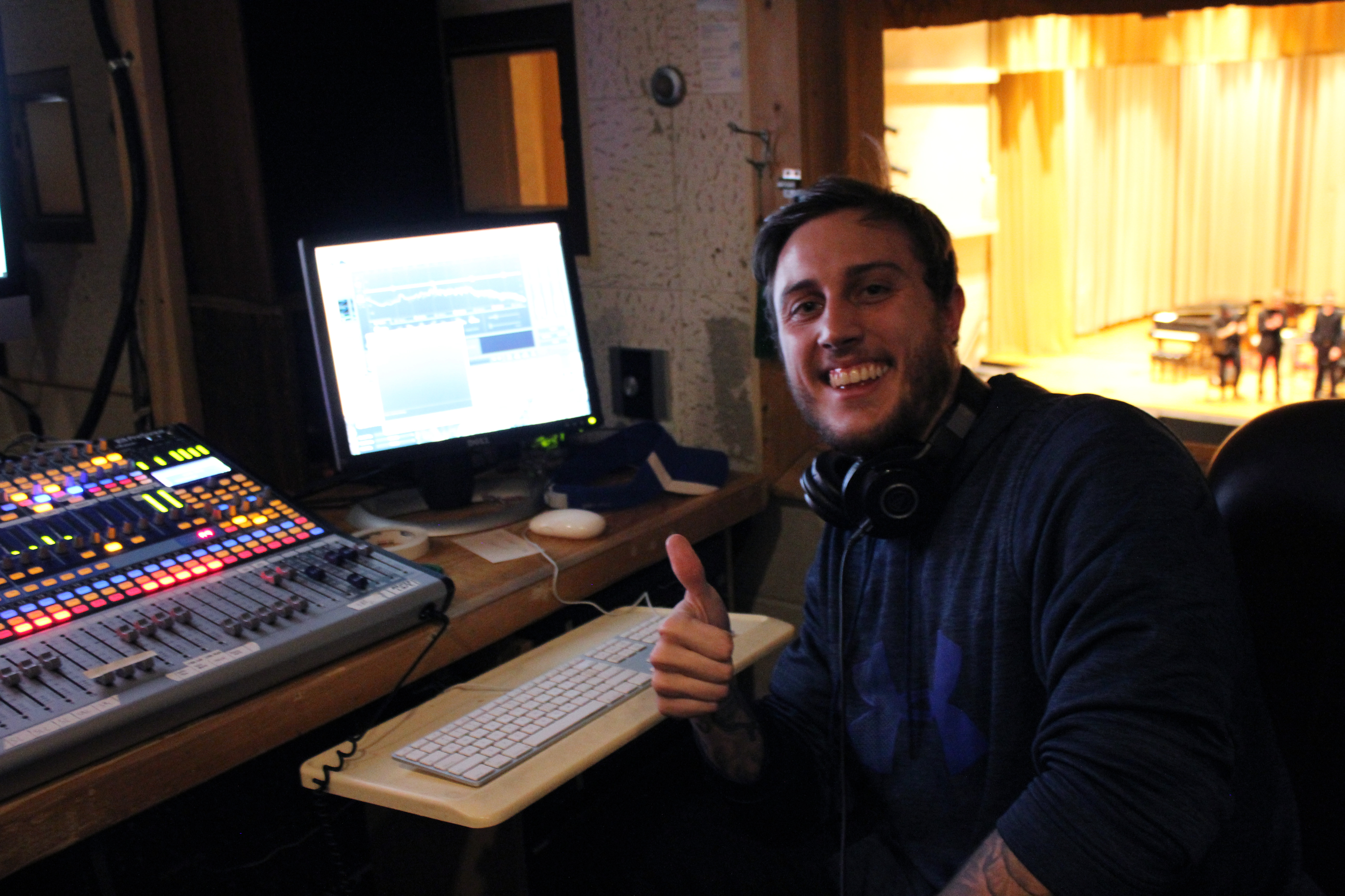 A student from the Department of Recording Industry smiles in front of sound mixing board in the School of Music's music hall