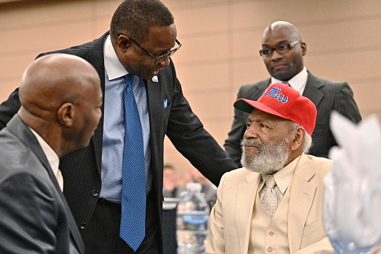 MTSU President Sidney A. McPhee, left, chats with civil rights trailblazer James Meredith, clad in white suit and red ball cap, the keynote speaker at the 23rd annual Unity Luncheon Feb. 14 at MTSU. (MTSU photo by J. Intintoli)