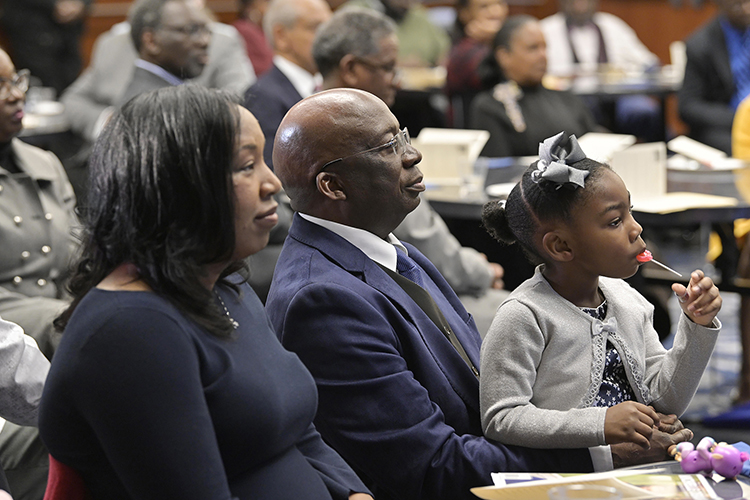 As he holds his daughter, Olivia, in his lap, Frank Michello, MTSU finance professor, center, listens to a tribute before receiving the 2019 John Pleas Faculty Recognition Award at a ceremony held Thursday, Feb. 21, in the Ingram Center at MTSU. The award, given to an outstanding minority faculty member, is named for John Pleas, MTSU Emeritus Professor of Psychology. At left is Michello's wife, Sonja. (MTSU photo by Andy Heidt)