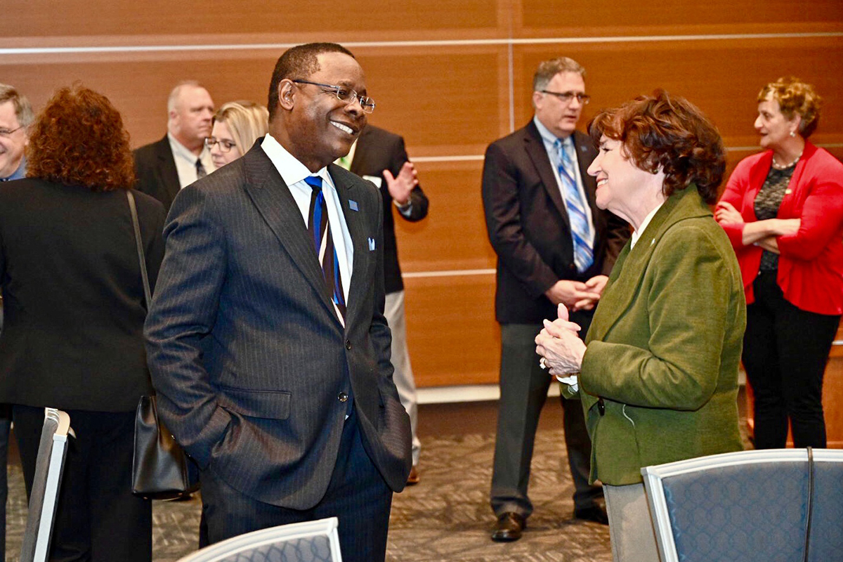 Presidents Sidney A. McPhee, left, of MTSU and Janet Smith of Columbia State Community College exchange greetings.