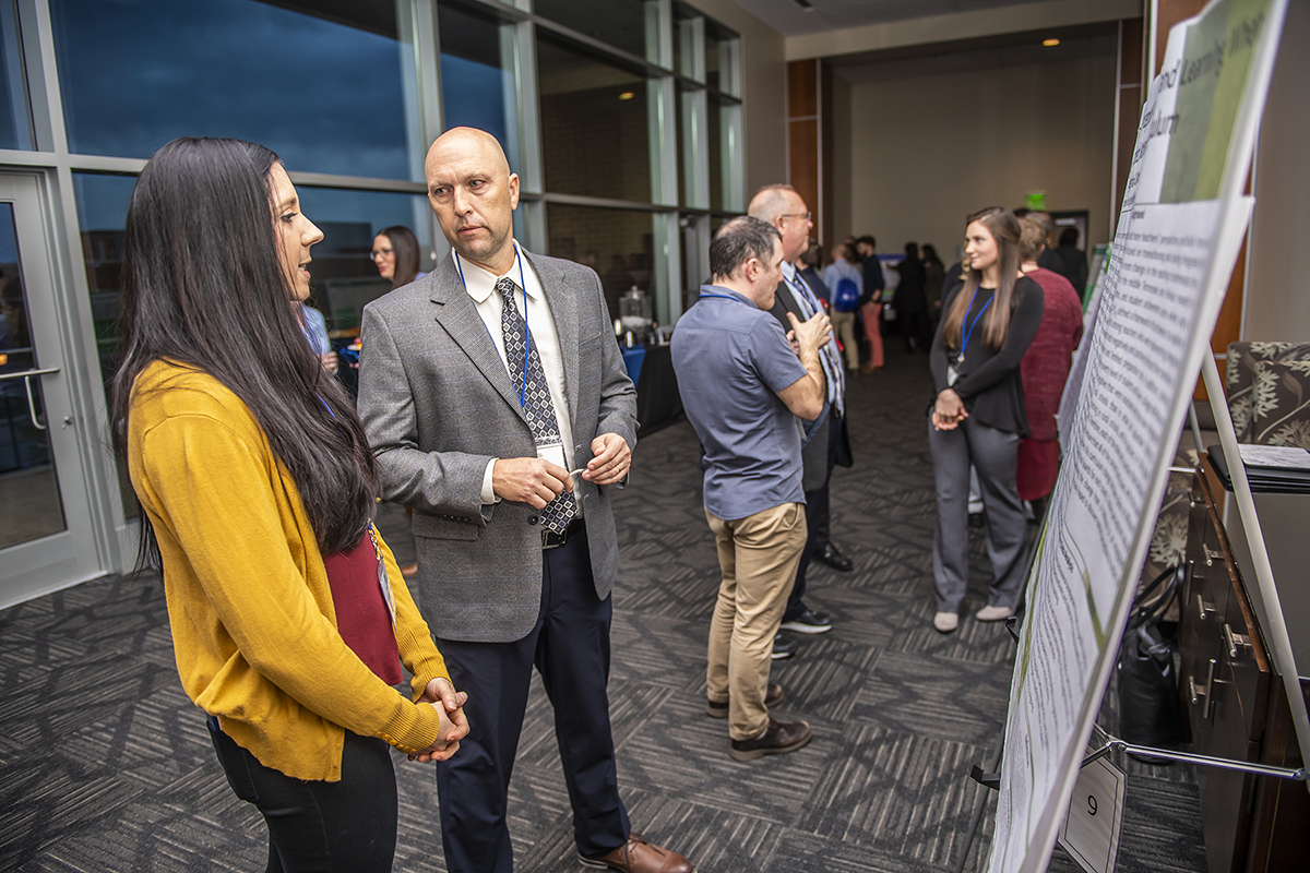 Tennessee STEM Education Center first-year Director Greg Rushton, right, learns about a research project a student conducted that was presented Feb. 14 during the center's 13th annual STEM conference in the Student Union Building. (MTSU photo by Eric Sutton)