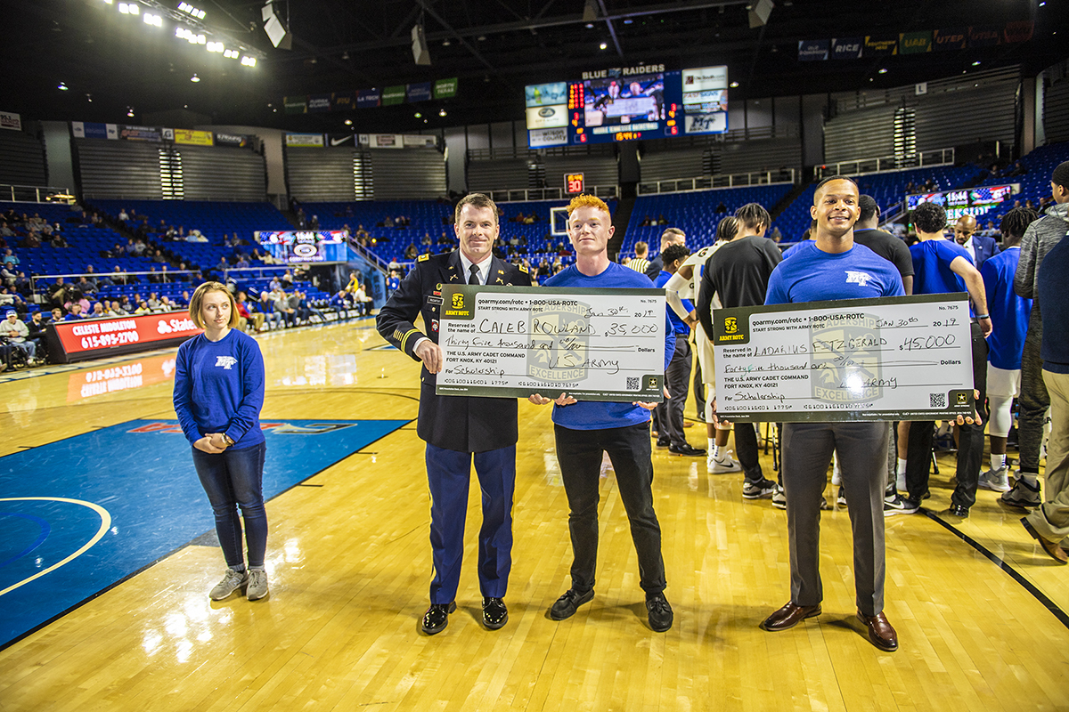 U.S. Army Lt. Col. Carrick McCarthy, center left, chair of MTSU's Department of Military Science, presents scholarships to Caleb Rowland, center right, and Ladarius Fitzgerald during Military Appreciation Night Jan. 30 in Murphy Center. Looking on at left is fellow new MTSU cadet Jordan Plumb. (MTSU photo by Eric Sutton)