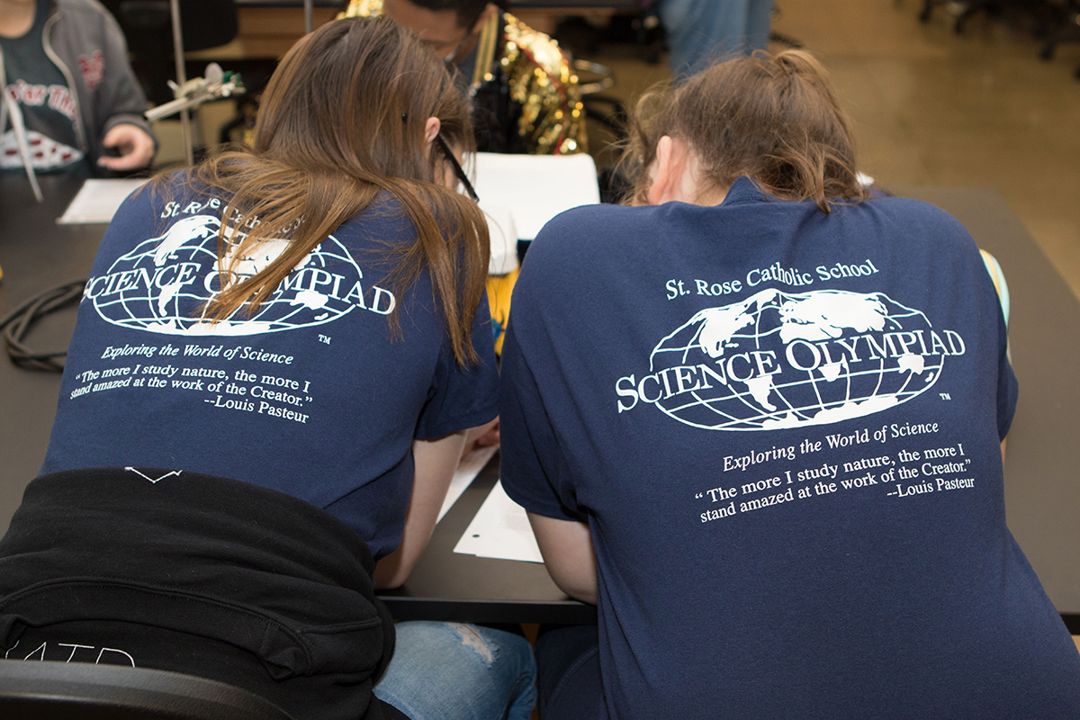 Hanna Fletcher and Kenley Baltz, eighth-graders at St. Rose of Lima Catholic School sport matching T-shirts as they work to record data for their water quality project during the 24th Regional Science Olympiad in the MTSU Science Building. (MTSU photo by James Cessna)