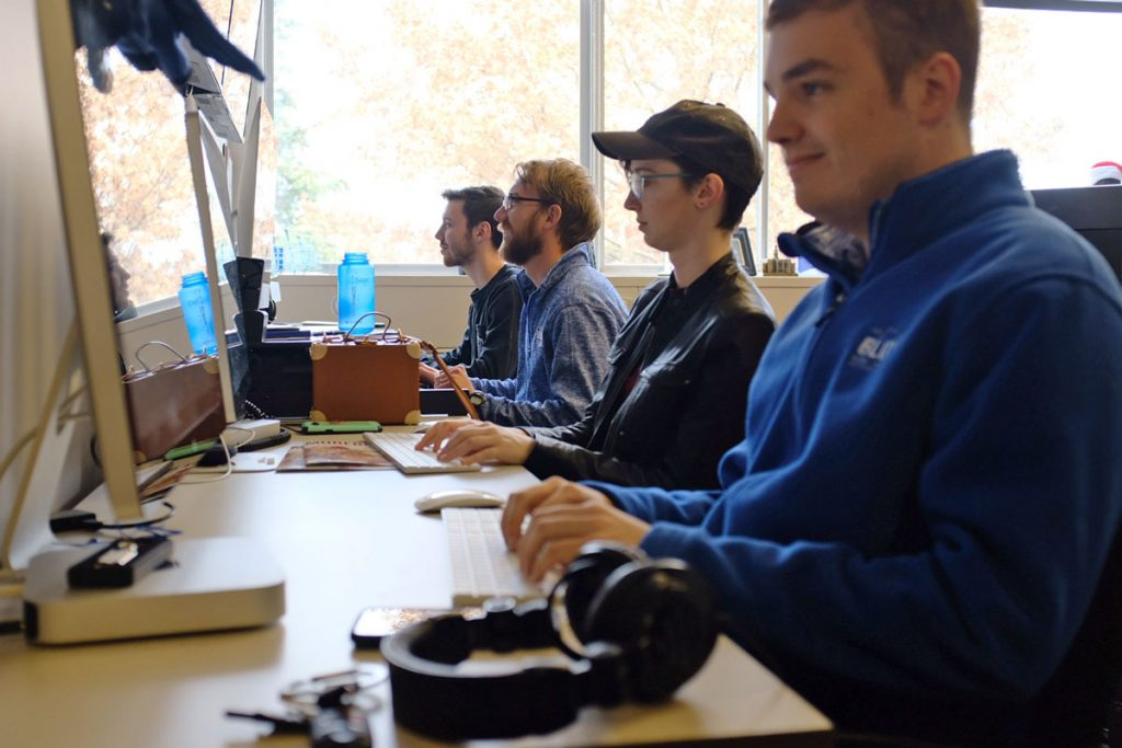 Student workers in the Office of Marketing & Communications sitting at desks with computers in front of them producing lifestyle blog content for the MTSU Student Voice. Photo: John Goodwin