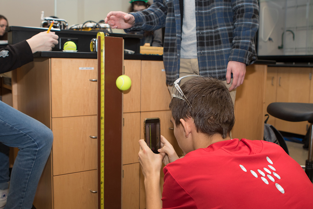 "Trevor Smith of Page High School in Franklin, Tenn., uses his cell phone to take a photo of the project he and his teammates worked to record data for the ""Experimental Design"" event at the 24th annual Regional Science Olympiad at MTSU Feb. 23. (MTSU photo by James Cessna)"