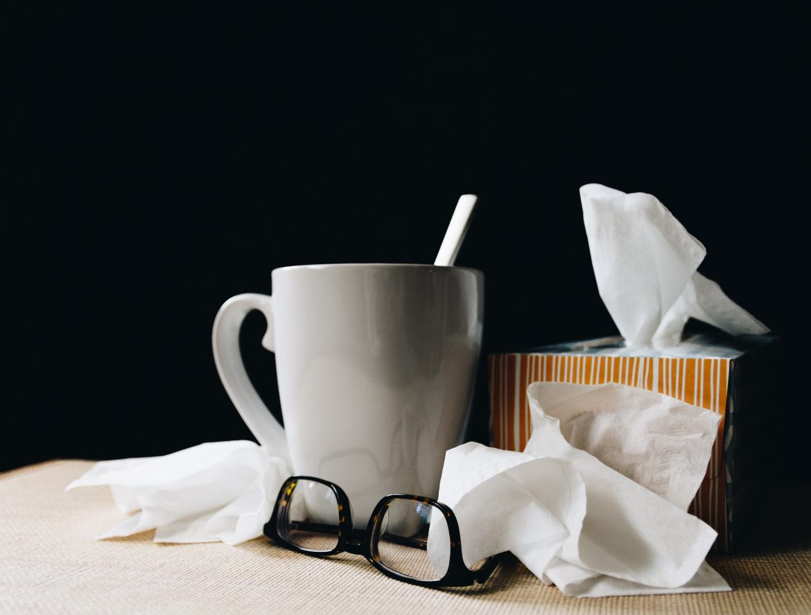 Image of a coffee mug and used tissues with a pair of glasses on a table top.