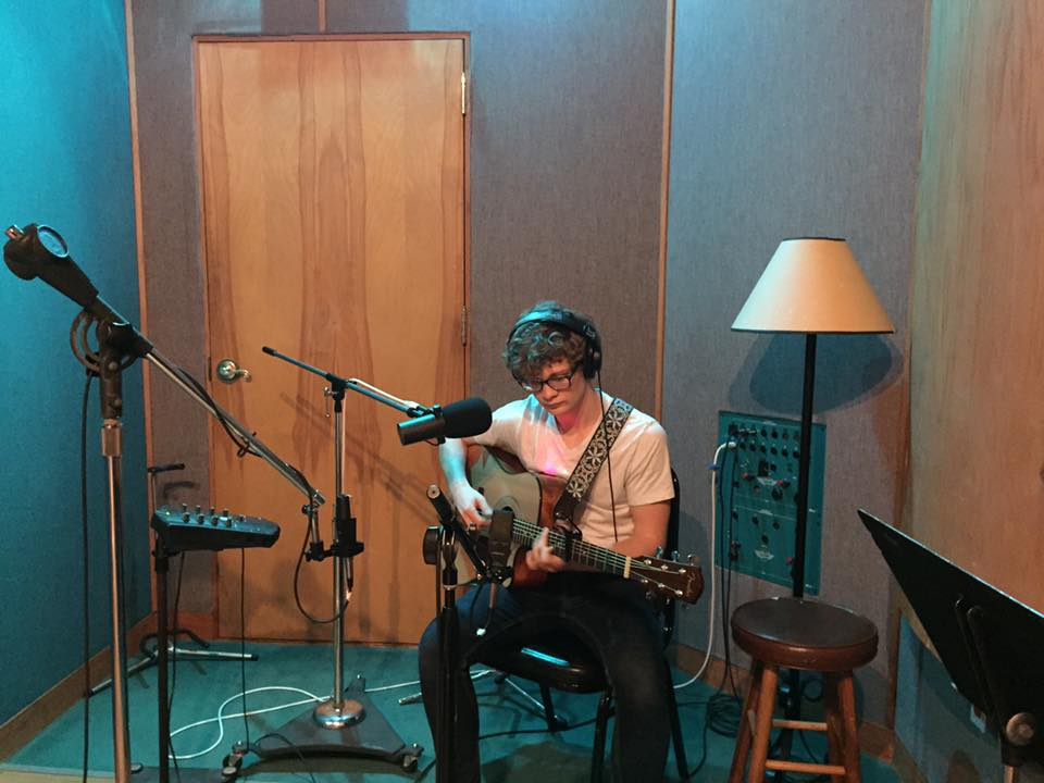 Cooper Gilliam, a Commercial Songwriting major, plays his guitar in a small recording studio room